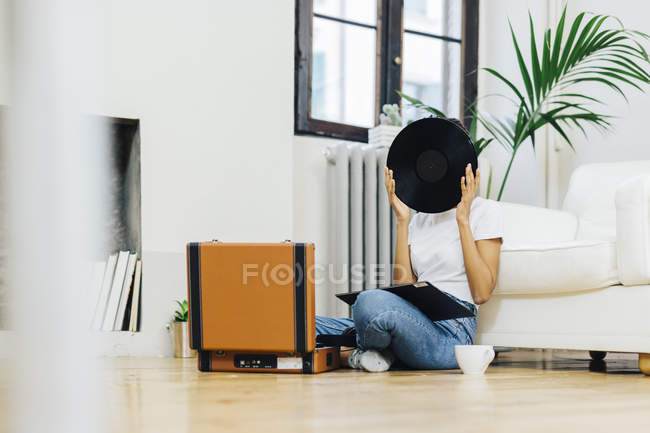 Молодая женщина сидит на земле и слушает музыку из проигрывателя, прячется за винилом — стоковое фото