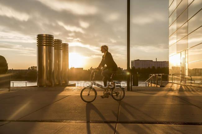 Femme âgée à vélo de ville au bord de la rivière au coucher du soleil — Photo de stock