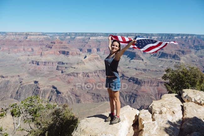 EUA, Arizona, mulher sorridente com bandeira americana no Grand Canyon National Park — Fotografia de Stock