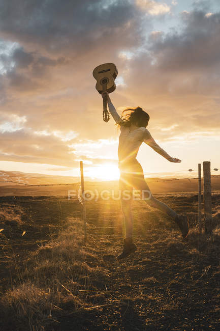 Ісландія, жінка стрибає з гітари на заході сонця — стокове фото
