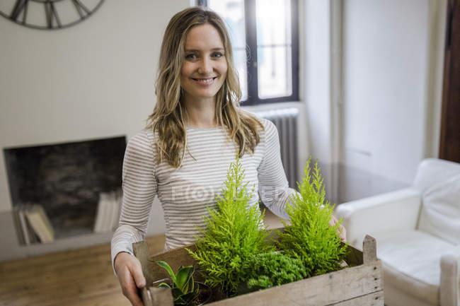 Porträt einer lächelnden Frau, die Kiste mit Pflanzen zu Hause trägt — Stockfoto