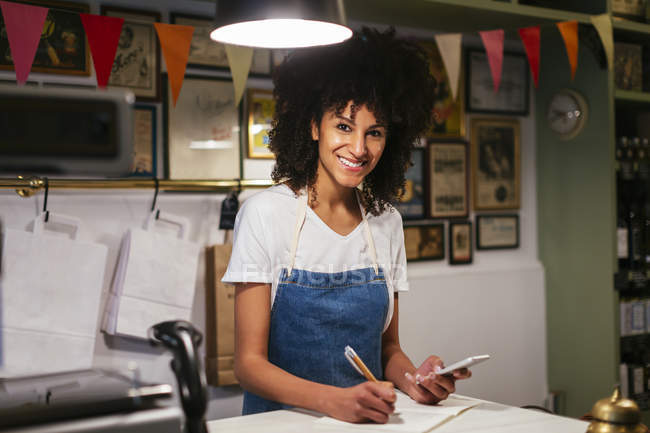 Portrait of smiling woman with cell phone and notebook in a store — Stock Photo