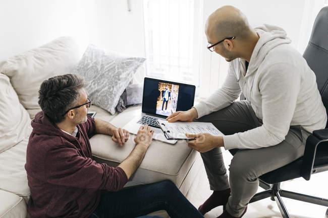 Dois colegas trabalhando em fotografia no laptop em casa — Fotografia de Stock