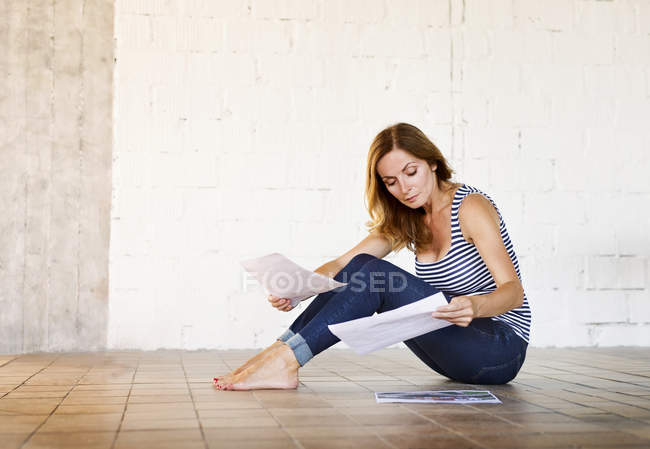 Woman sitting on the floor reviewing paper — Stock Photo