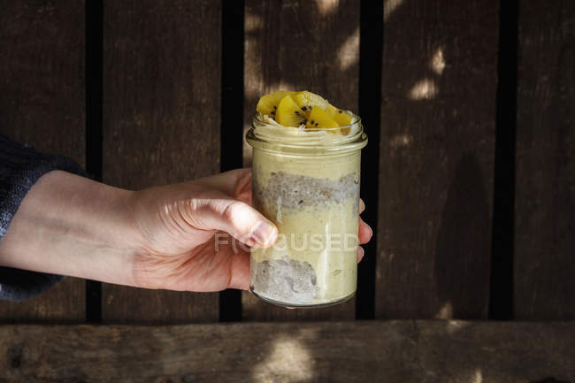 Mão do homem que prende o vidro do pudim de Chia com smoothie da manga decorado com quivi — Fotografia de Stock