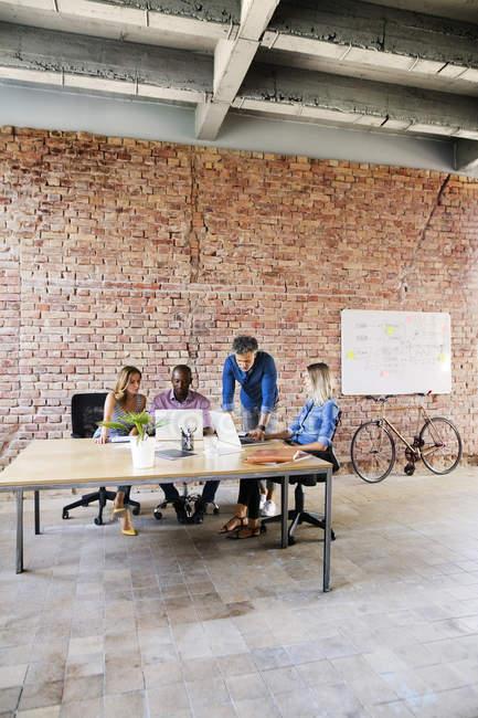 Geschäftsleute mit Laptops diskutieren am Schreibtisch im Büro — Stockfoto