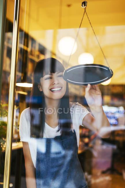 Щаслива жінка поворот увійти у вікно магазину — стокове фото