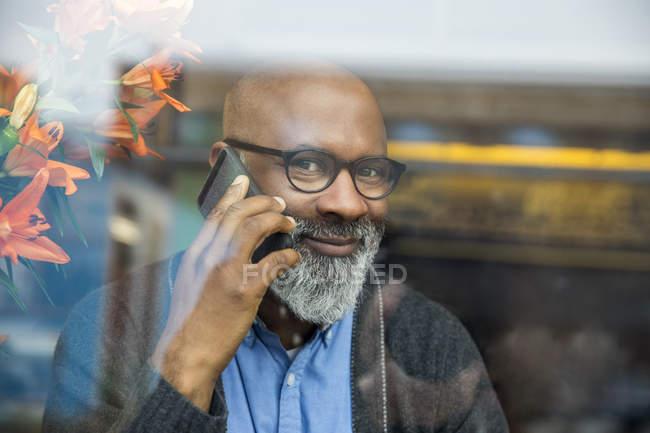 Porträt eines lächelnden afrikanischen amerikanischen Mannes auf dem Telefon hinter Fensterscheibe — Stockfoto