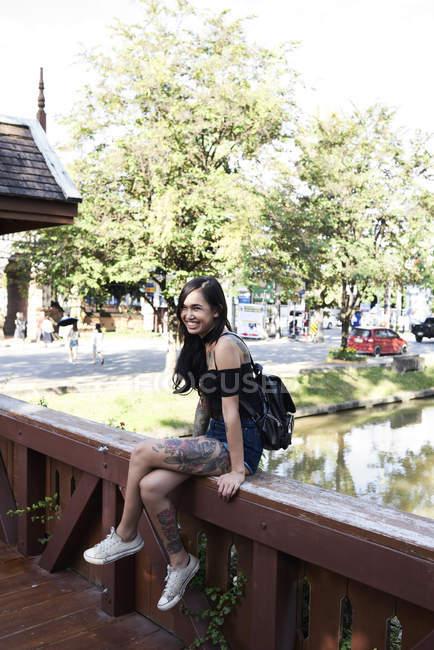 Портрет счастливой татуированной женщины, сидящей на деревянном мосту — стоковое фото
