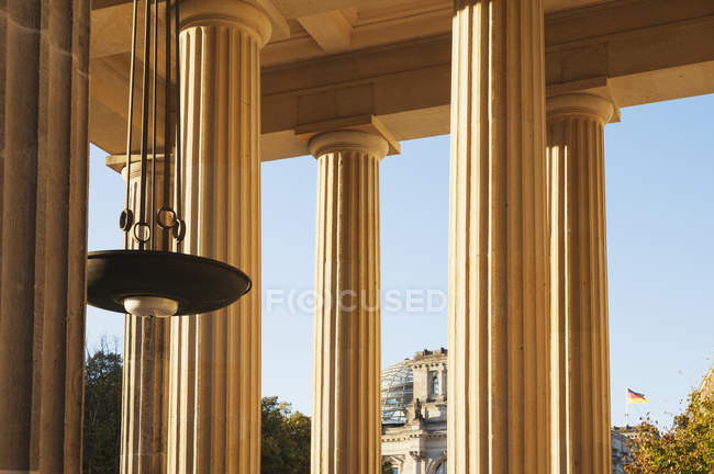 Germany, Berlin, columns of Brandenburger Tor, Reichstag building in background - foto de stock