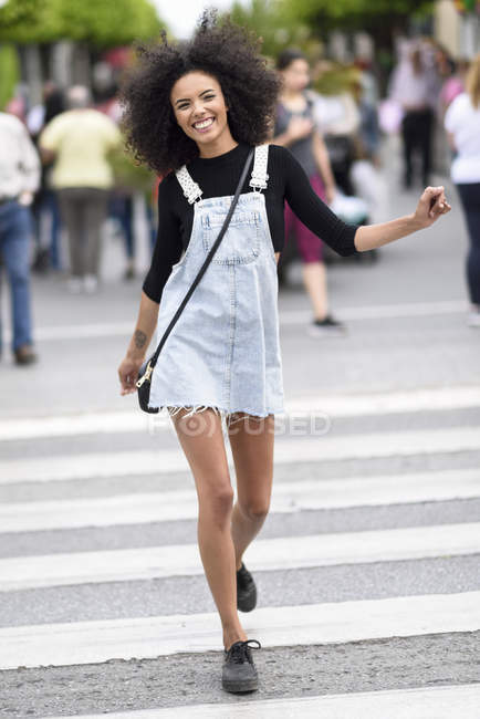 Portrait of happy young woman walking on zebra crossing — Stock Photo