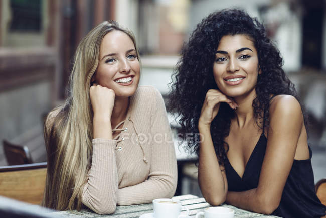 Portrait of two friends sitting in sidewalk cafe watching something — Stock Photo