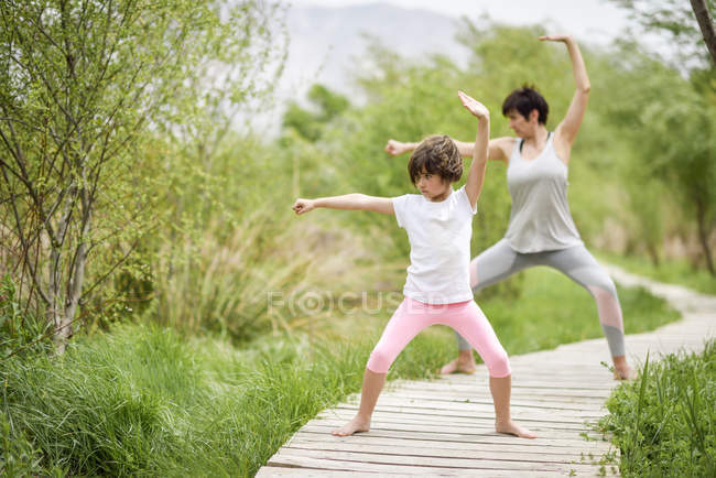 Mother and daughter doing yoga on boardwalk — Stock Photo