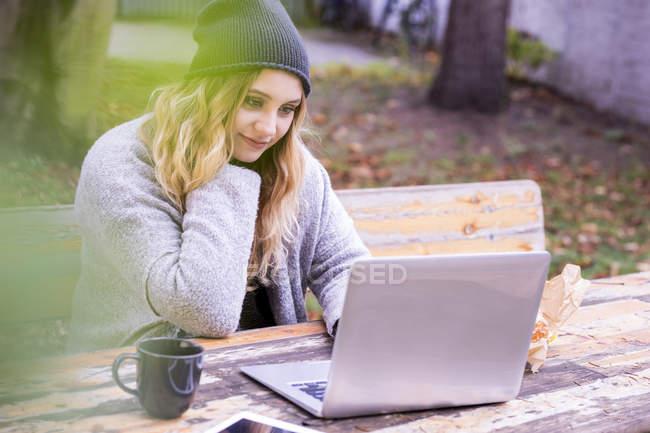 Портрет усміхнена молода жінка з ноутбуком Skyping на відкритому повітрі восени — стокове фото