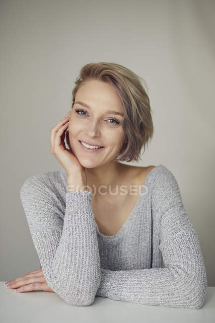 Portrait de femme blonde souriante portant un pull gris — Photo de stock