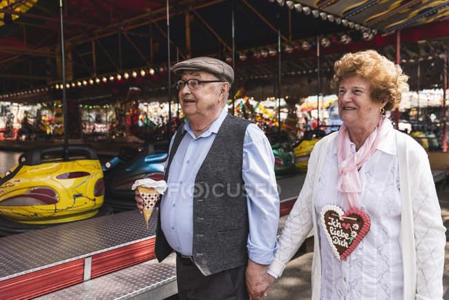Felice coppia anziana camminando mano nella mano sulla fiera — Foto stock