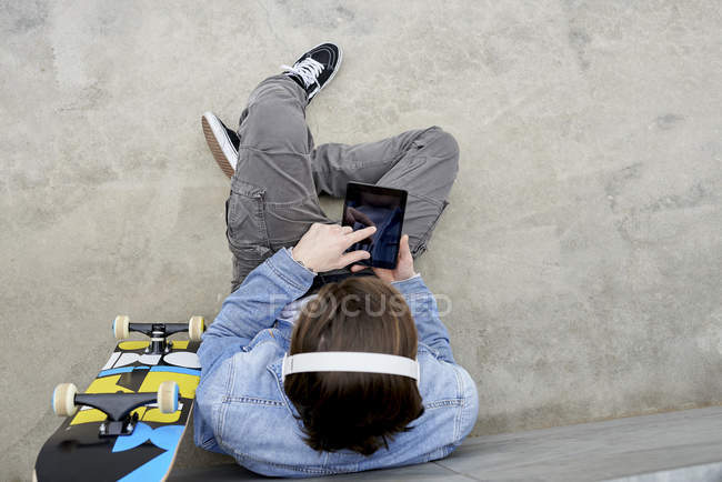 Young man with skateboard sitting on ground, using digital tablet — Stock Photo