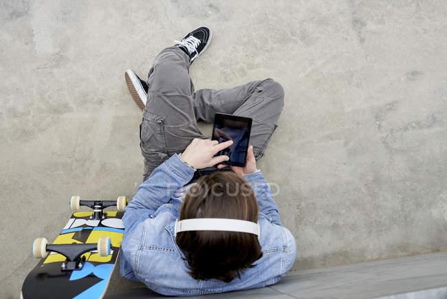 Junger Mann mit Skateboard auf dem Boden sitzend, mit digitalem Tablet — Stockfoto