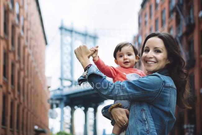 USA, New York, New York, Madre felice che tiene in braccio un bambino a Brooklyn con Manhattan Bridge sullo sfondo — Foto stock