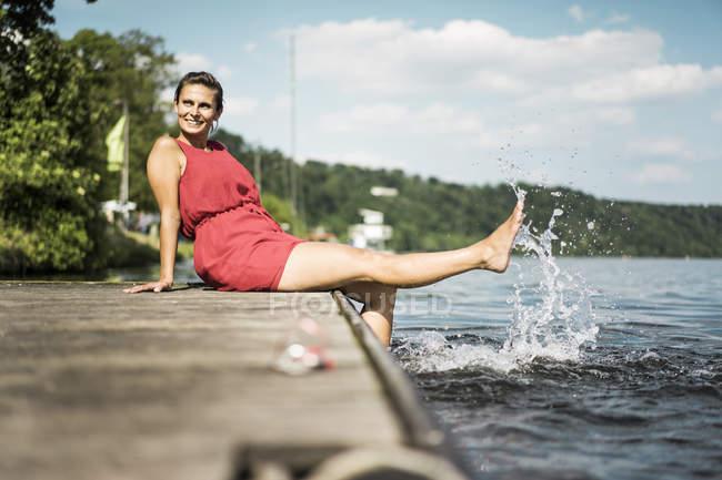 Glückliche Frau sitzt auf Steg an einem See — Stockfoto