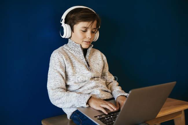 Menino sentado no banco usando fones de ouvido e usando laptop — Fotografia de Stock