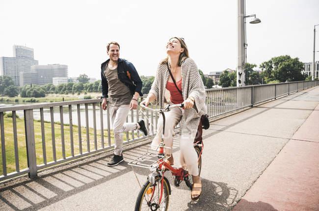 Joyeux couple traversant un pont à vélo et à pied — Photo de stock