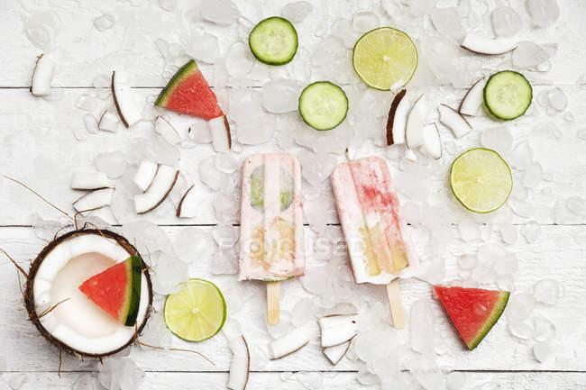 Lollies caseiros do gelo do coco da melancia com fatias do Cal e do pepino, coco fresco e partes da melancia em cubos de gelo — Fotografia de Stock