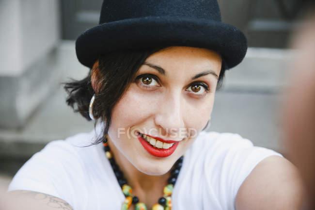 Портрет усміхненої жінки з капелюхом робить самовідвагу. — стокове фото