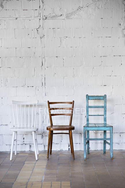 Chaises vides contre le mur blanc de brique — Photo de stock