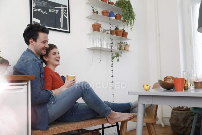 Coppia felice seduto in cucina, appoggiato l'uno contro l'altro — Foto stock