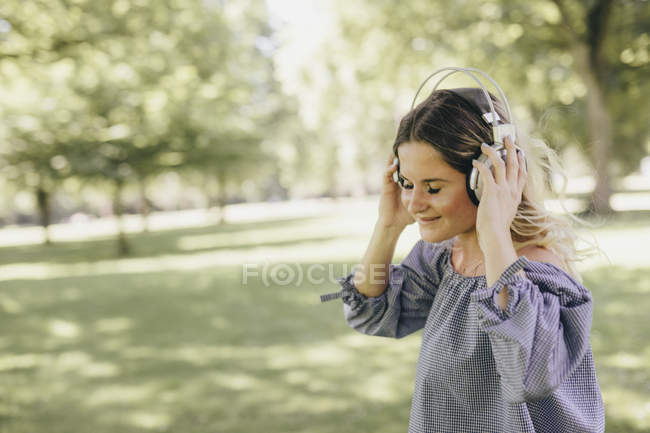 Smiling young woman in a park enjoying listening to music with headphones — Stock Photo