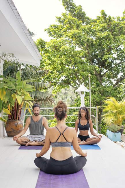 Две женщины и мужчина практикующие йогу на террасе — стоковое фото