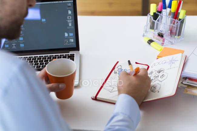 Homme dessinant dans un carnet au bureau — Photo de stock