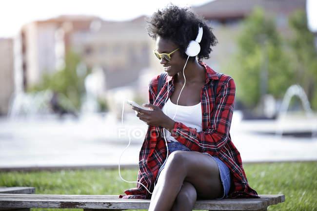 Sorrindo jovem mulher sentada no banco no parque da cidade ouvindo música com fones de ouvido — Fotografia de Stock
