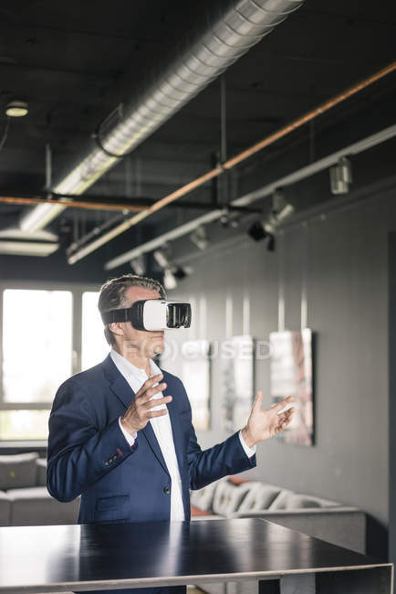 Mature businessman wearing VR glasses — Stock Photo