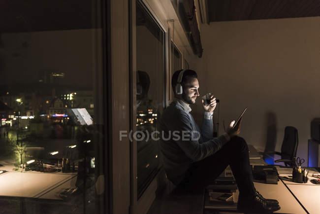 Homme d'affaires assis sur le rebord de la fenêtre dans le bureau la nuit écoutant de la musique avec écouteurs — Photo de stock