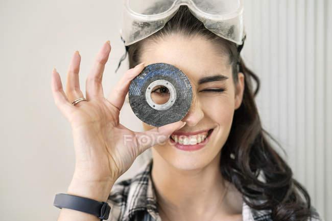 Молодая женщина ремонтирует свою новую квартиру, просматривает шлифовальный диск — стоковое фото