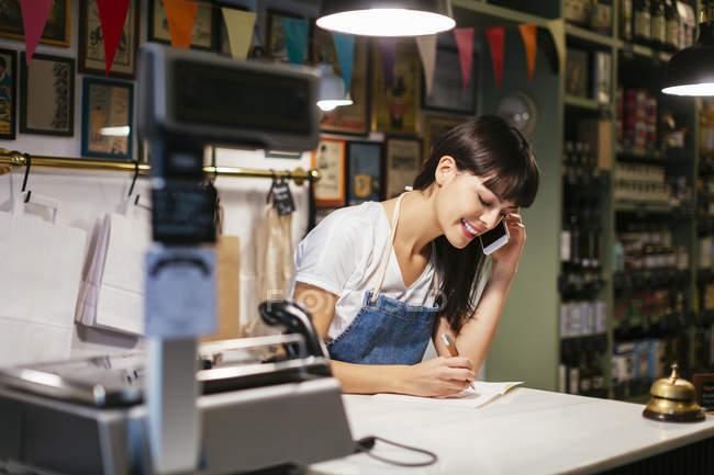 Улыбающаяся женщина по телефону в магазине делает заметки — стоковое фото