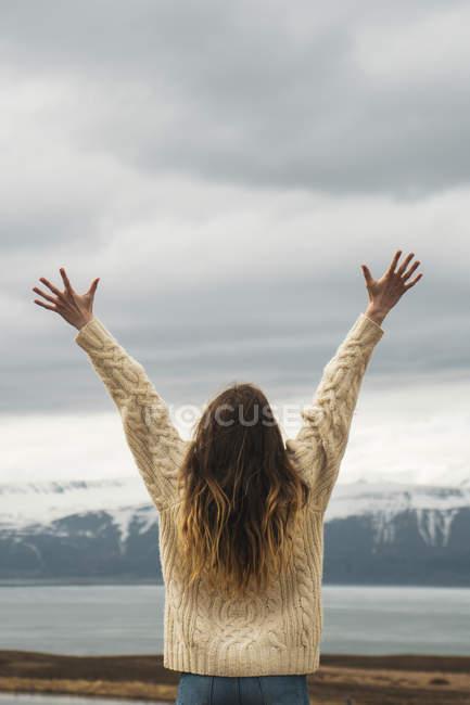 Islande, femme debout au bord du lac avec les bras levés — Photo de stock