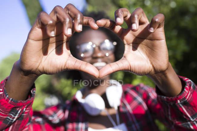 Las manos de la mujer dando forma al corazón - foto de stock