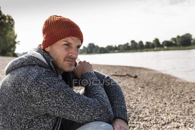 Reifer Mann mit roter Mütze sitzt am Rheinufer — Stockfoto