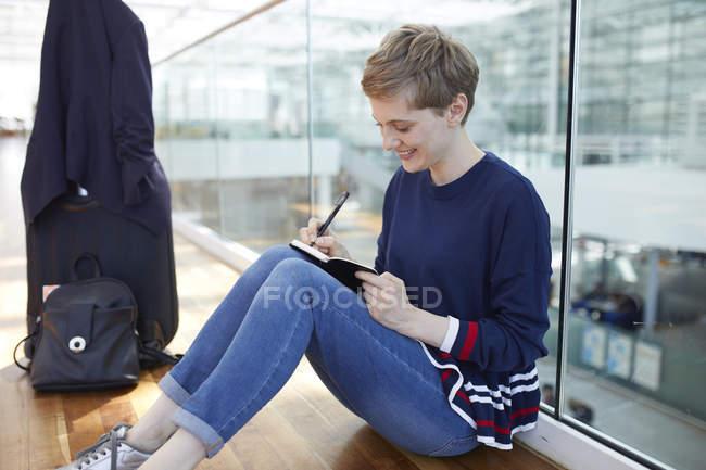Mujer de negocios rubia sentada en el suelo, escribiendo en un cuaderno - foto de stock