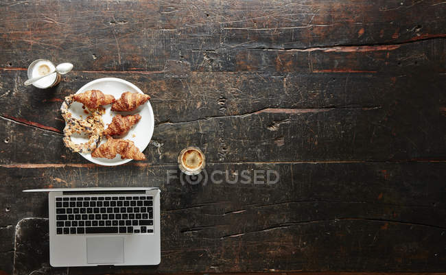 Breakfast table with laptop, top view — Stock Photo