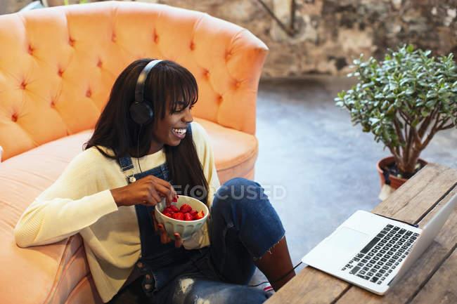 Lachende junge Frau, die mit Laptop und Kopfhörer auf dem Boden ihres Lofts sitzt — Stockfoto