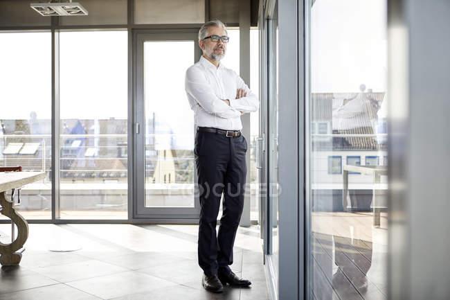 Бизнесмен, выглядывающий в окно — стоковое фото