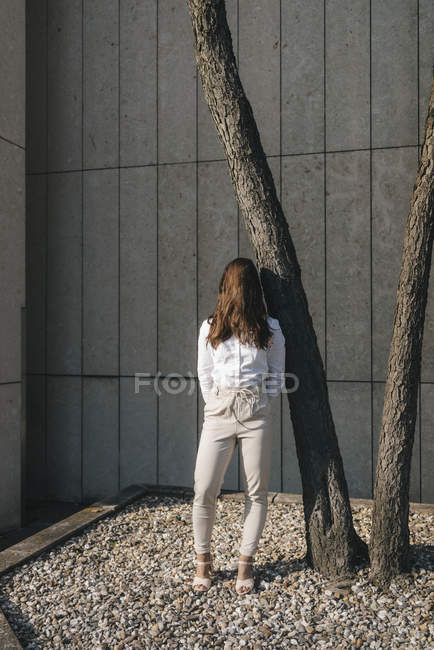 Young businesswoman standing in backyard, face coverd with hair — Stock Photo