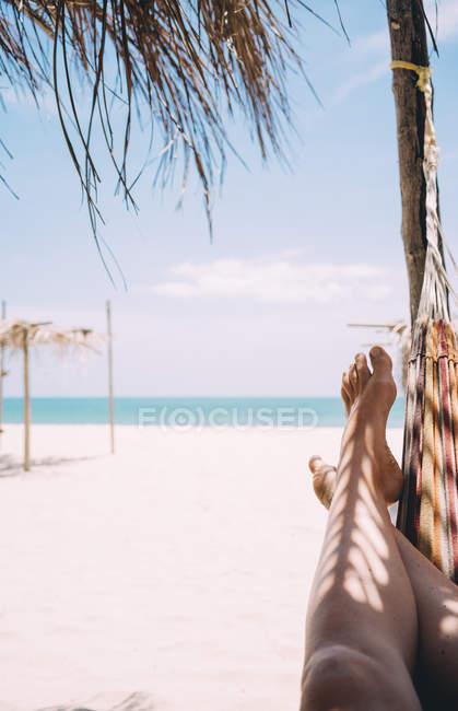 Thailand, Koh Lanta, legs of woman lying in hammock on the beach — Stock Photo