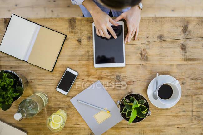 Vista dall'alto della donna alla scrivania in legno con notebook, cellulare e tablet — Foto stock