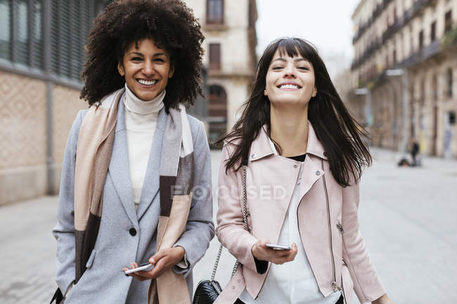 Spain, Barcelona, portrait of two female friends with cell phones walking in city — Stock Photo