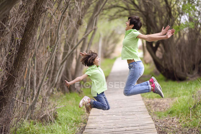 Happy mother and daughter jumping on boardwalk — Stock Photo